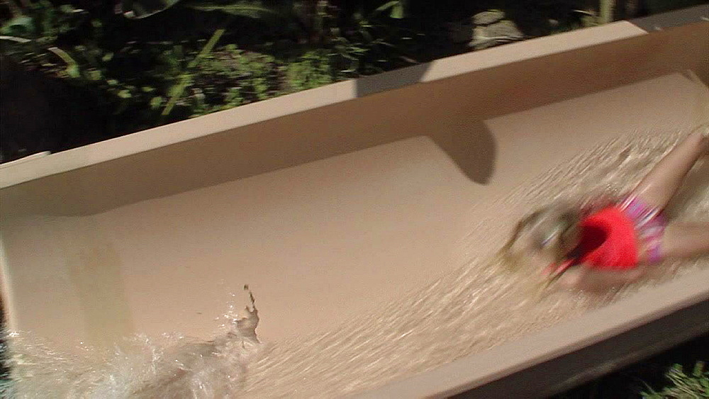 Blond haired girl slipping down a water slide