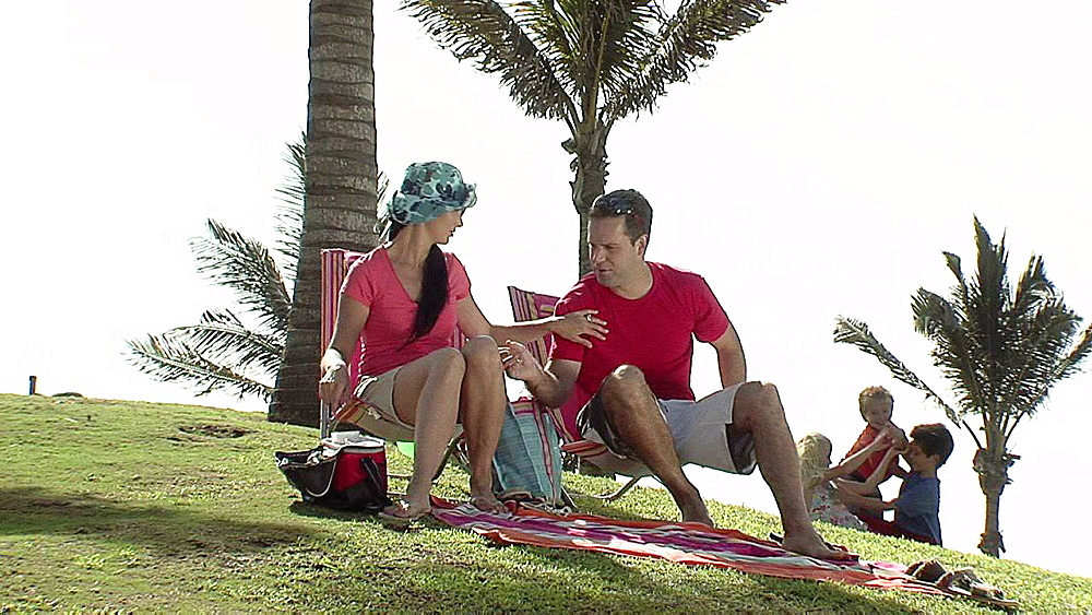 Man and woman sitting whilst children play around them