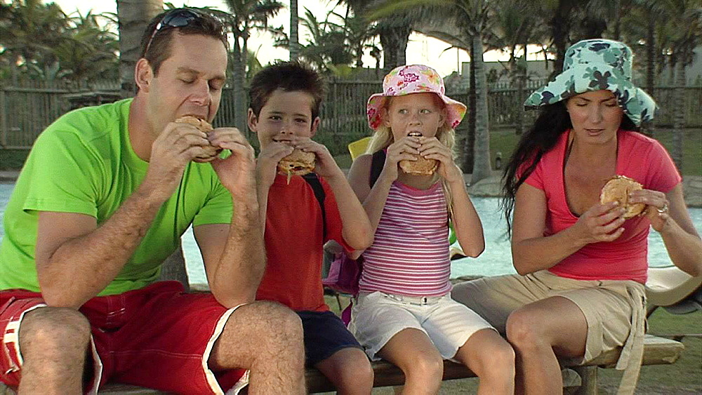 Man and woman and their kids eating a burger