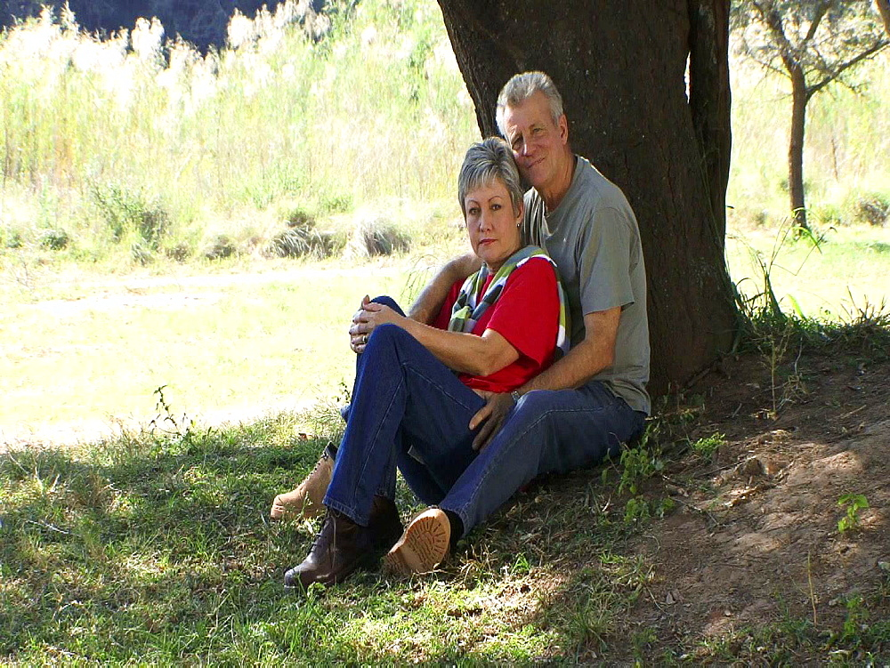 Couple sitting up against a tree cuddling
