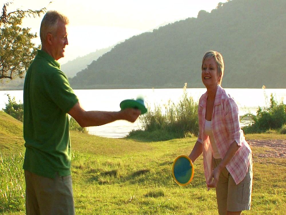 Man wearing a green Tshirt throwing a ball to a woman