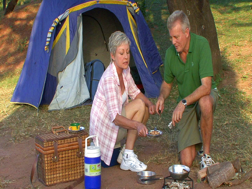 Man and woman by their tent making sausages