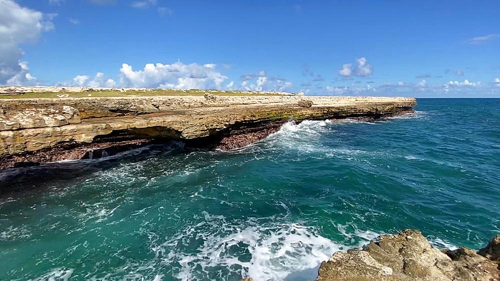 Turquoise waves crash against Devil's Bridge limestone rock formation, Antigua, Leeward Islands, West Indies, Caribbean, Central America