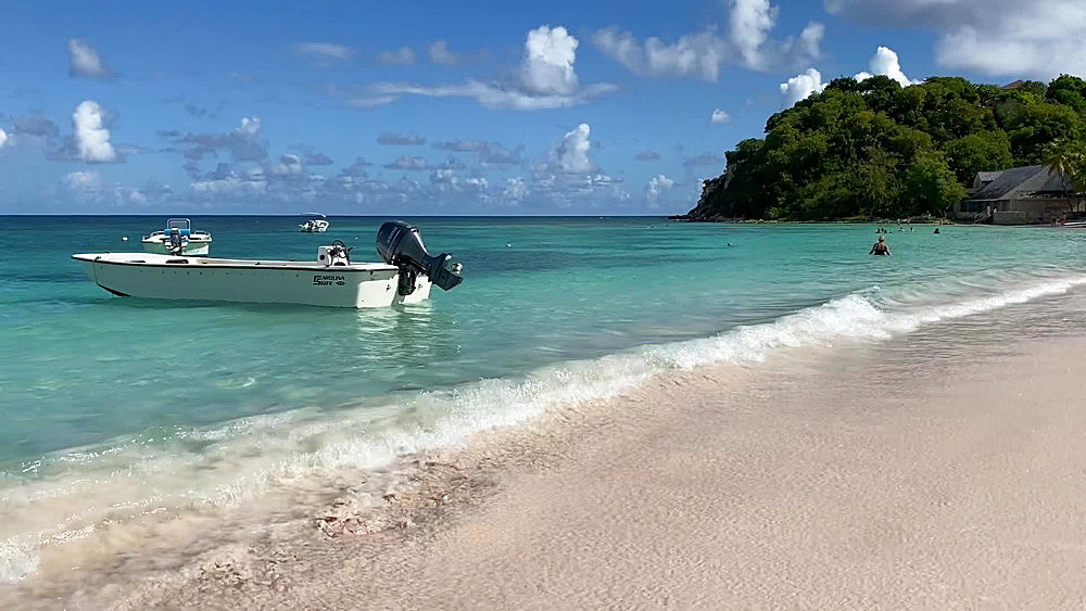 Small boat bobbing in calm turquoise waters lapping on to fine sand of Long Bay Beach, Antigua, Leeward Islands, West Indies, Caribbean, Central America
