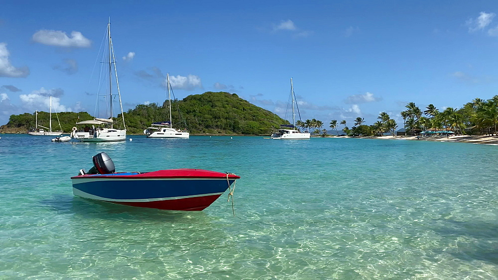 Small boat bobbing in calm turquoise waters lapping on to fine sand of Saltwhistle Bay Beach, Mayreau, Grenadines, West Indies, Caribbean, Central America