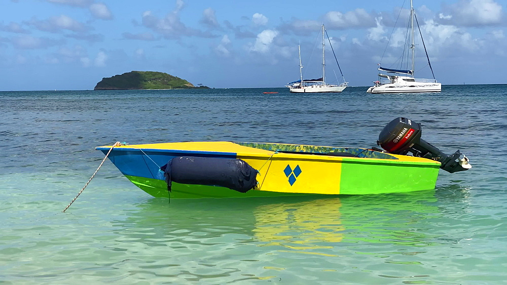 Small boat in St. Vincent colours bobbing in calm turquoise waters, Saltwhistle Bay Beach, Mayreau, Grenadines, West Indies, Caribbean, Central America