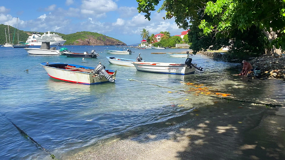 Man cleans fish in tropical Les Saintes bay, boats, cruise ship, Terre de Haut island, Iles des Saintes, Guadeloupe, Caribbean