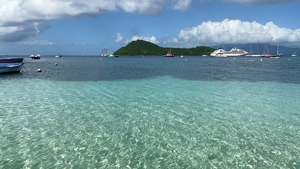 Tropical Les Saintes bay, ripples on calm turquoise water, small boats, cruise ship, Terre de Haut island, Guadeloupe, West Indies, Caribbean, Central America