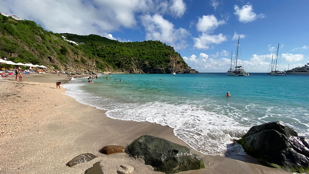 Bathers in turquoise sea and on walking on beach, lapping waves, anchored yachts, Shell Beach, Gustavia, St Barths, Caribbean