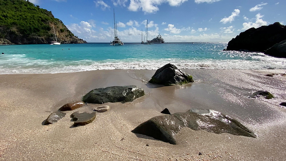 Turquoise sea swirls around beautiful beach rocks, lapping waves, anchored yachts, Shell Beach, Gustavia, St Barths, Caribbean