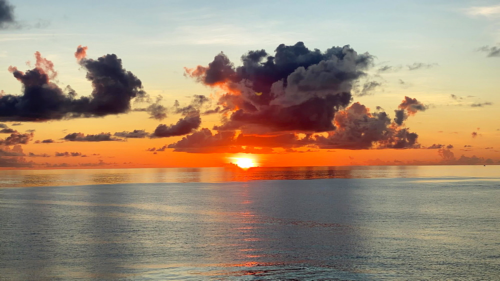 Vibrant sunset over a calm sea with ripples, from a cruise ship off Southern St. Kitts, West Indies, Caribbean, Central America