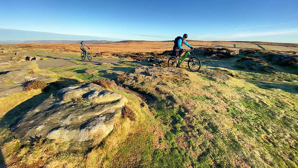 Mountain bikers cycle in winter sun on the moor on top of Curbar Edge, Peak District National Park, Derbyshire, England, United Kingdom, Europe