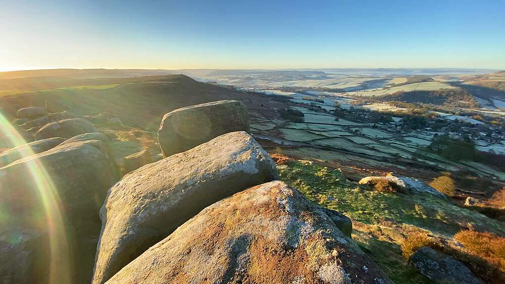 Walkers view, peering over rocky Curbar Edge, frosty Derwent Valley beyond, Peak District National Park, Derbyshire, England, United Kingdom, Europe