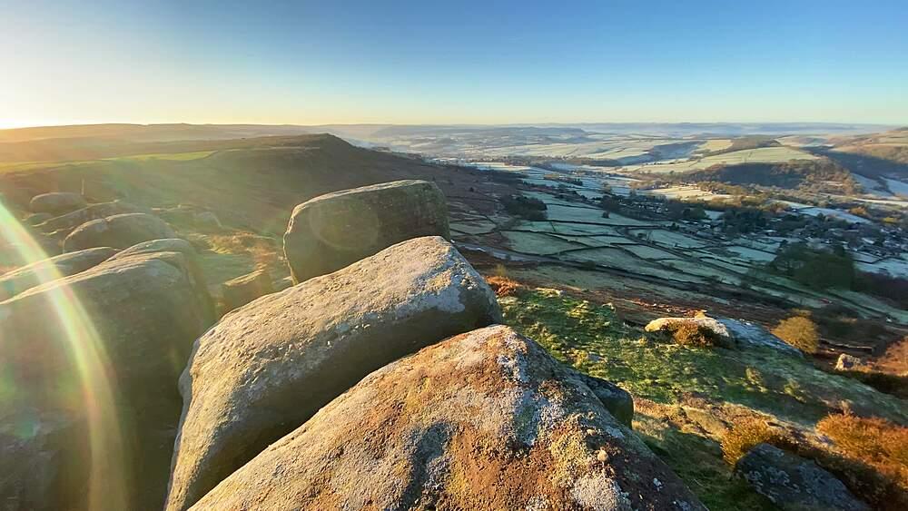 Walkers view, peering over rocky Curbar Edge, frosty Derwent Valley beyond, Peak District National Park, Derbyshire, England, United Kingdom, Europe