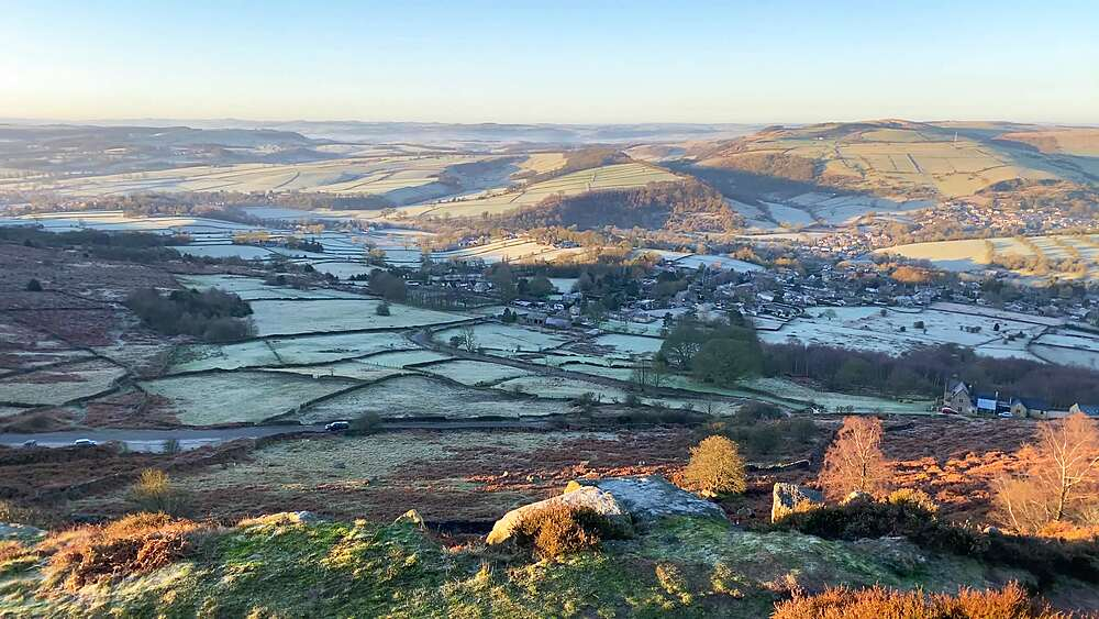 Car travels towards Curbar Edge from frosty Derwent Valley, low winter sun, Peak District National Park, Derbyshire, England, United Kingdom, Europe