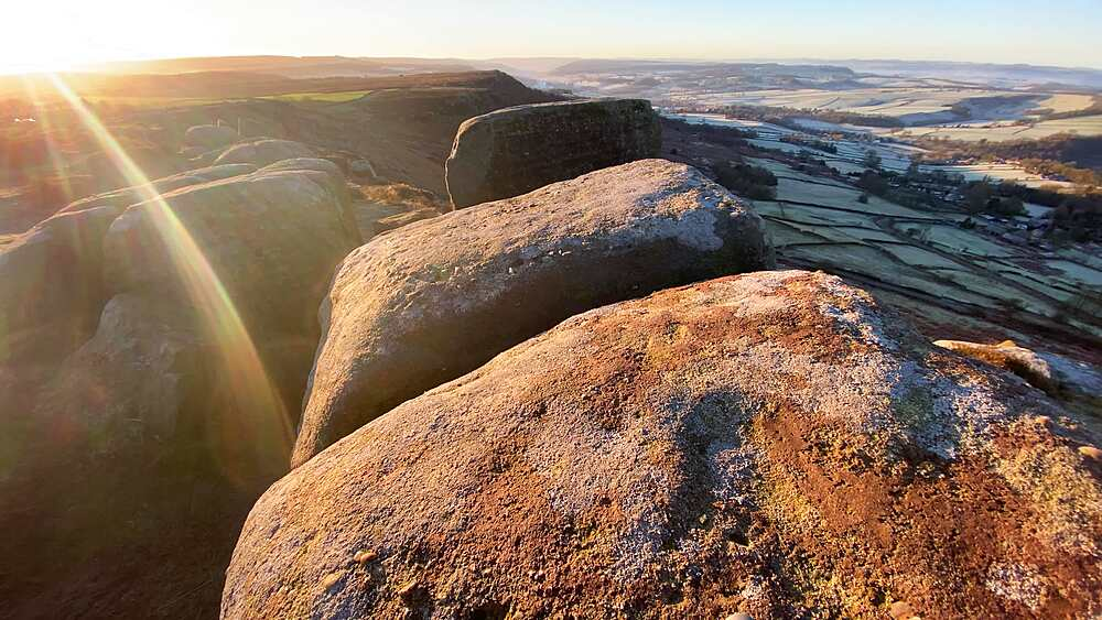 Lichen covered rocks of Curbar Edge, frosty Derwent Valley beyond, Peak District National Park, Derbyshire, England, United Kingdom, Europe