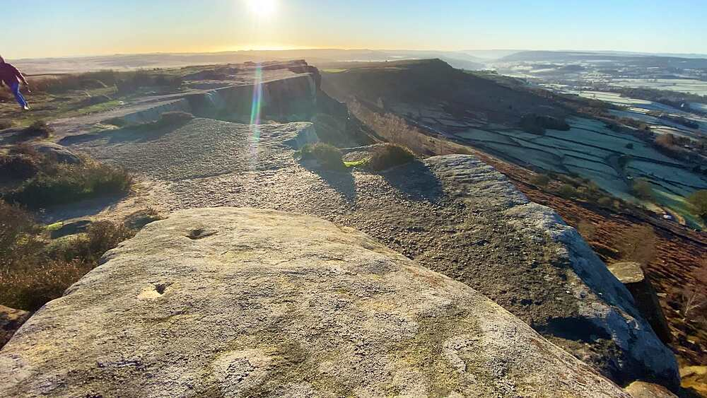 Walking dogs in low winter sun on frosty Curbar Edge, panoramic valley view, Peak District National Park, Derbyshire, England, United Kingdom, Europe
