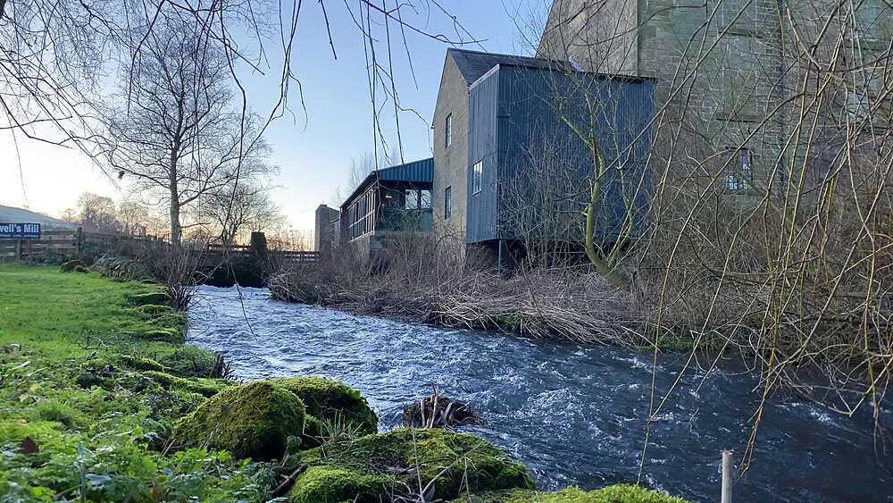 Low angle view of river, Caudwells Mill and moss, Grade II listed historic water power mill, in winter, Rowsley, Derbyshire, England, United Kingdom, Europe