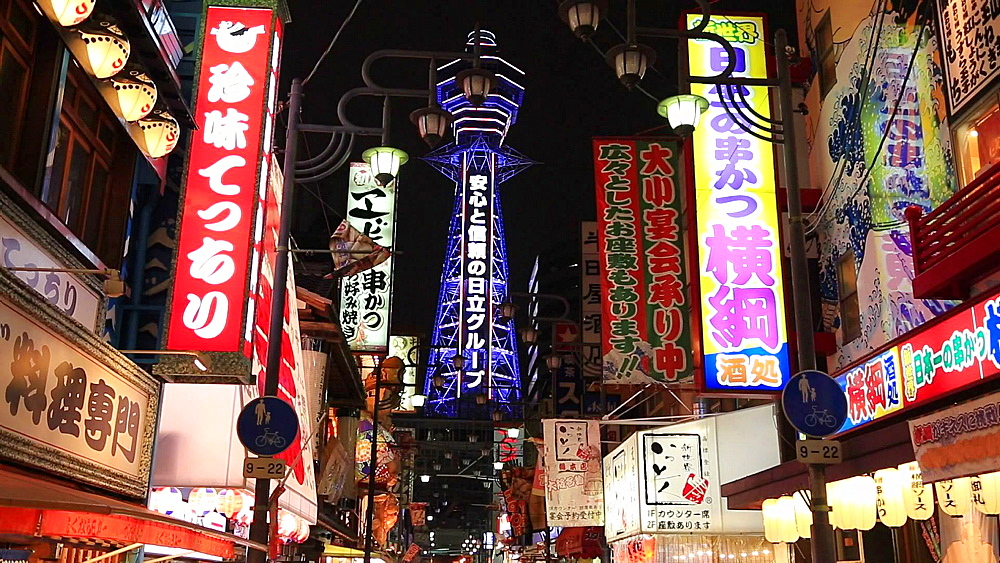 Osaka, JP - January 24, 2015:  Shop lights and Tsutenkaku Tower are lighted up at Shinsekai shopping district in Osaka, Japan. - 1172-1568