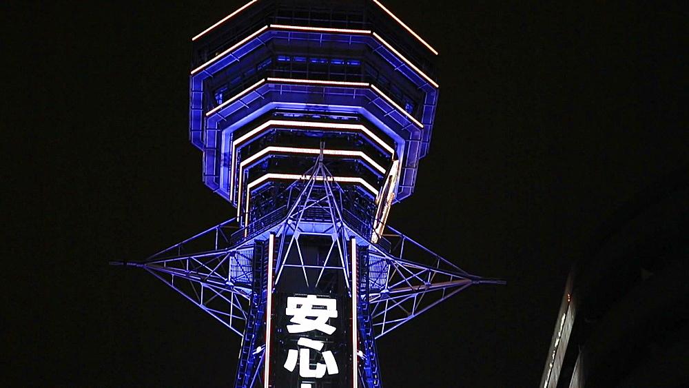 Osaka, JP - January 24, 2015:  The 91-meters-tall Tsutenkaku Tower is illuminated by neon lights at Shinsekai shopping district in Osaka, Japan. - 1172-1579