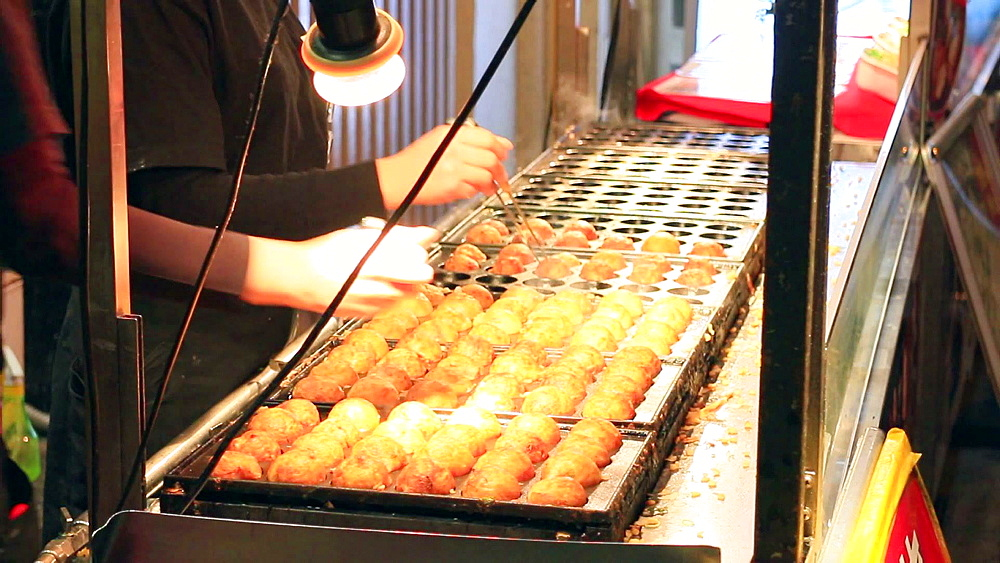 Osaka, JP - January 24, 2015:   Takoyaki (Octopus balls) being prepared at Dontonbori district in Osaka, Japan. - 1172-1586