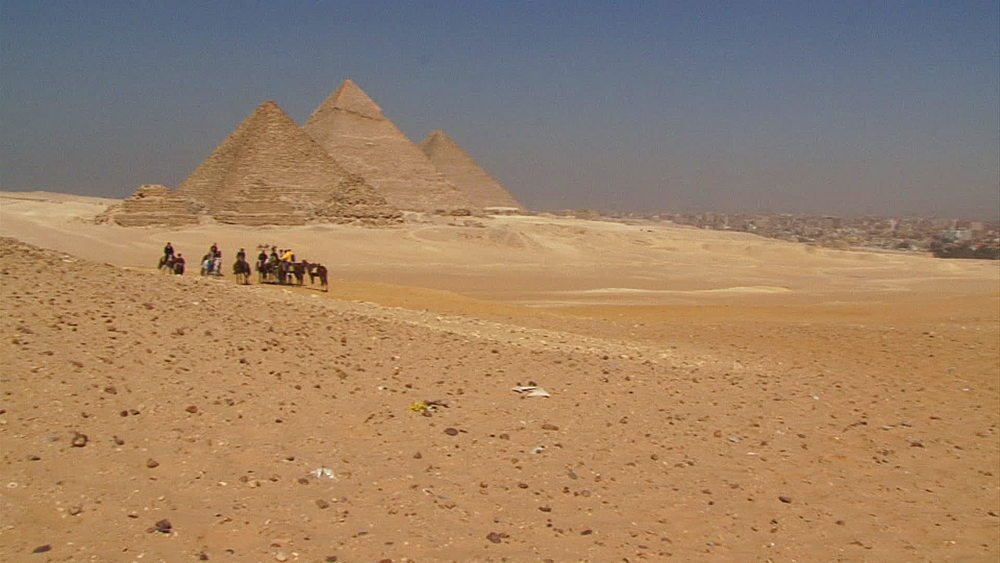 Pan from desert to pyramids in the Giza plateau at the edge of the Sahara Desert and group of people sitting on horses, Cairo, Egypt, Africa