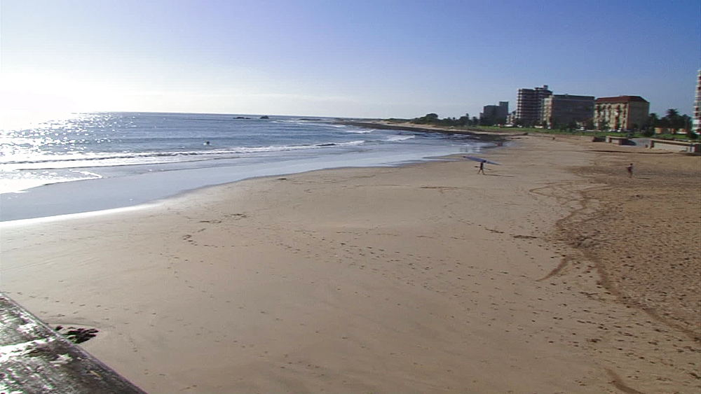 Pan from a boardwalk to the beach and buildings/ shops/houses, East London beachfront, South Africa - 1182-142