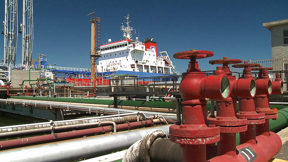 Oil tanker sitting in harbour with pipes, cranes and valves in foreground, Cape Town Harbour, South Africa - 1182-156
