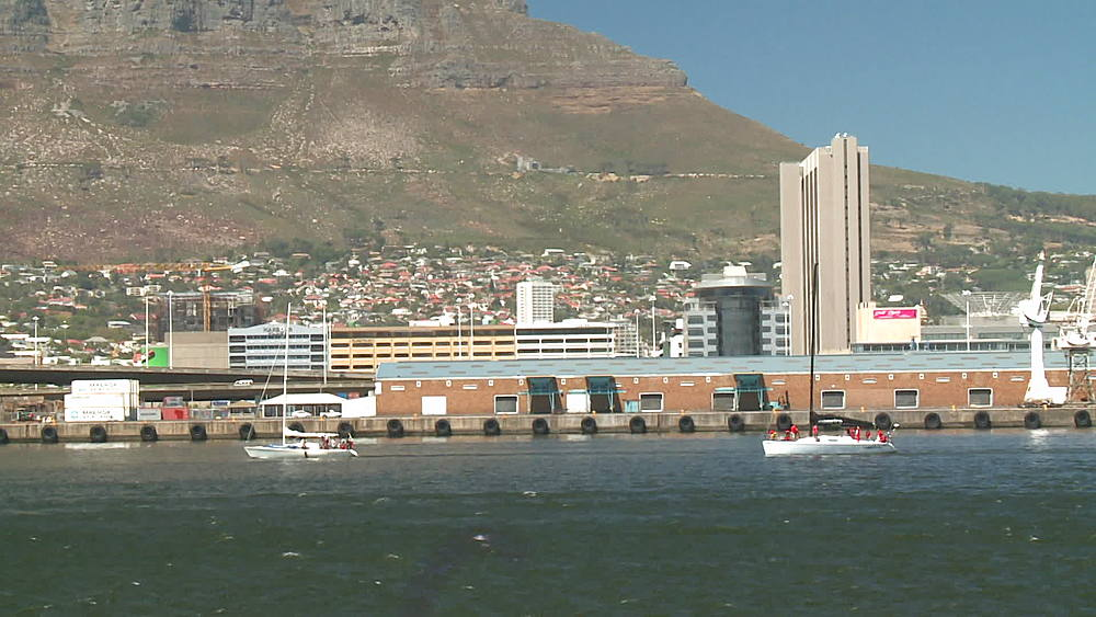 Two yachts sailing into Cape Town Harbour, windy, choppy seas, South Africa