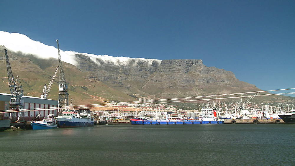 The 'Southern Valour' Oil Tanker berthed at an Oil Refinery in Cape Town, Harbour cranes at the base of Table Mountain with clouds rolling over, South Africa - 1182-173