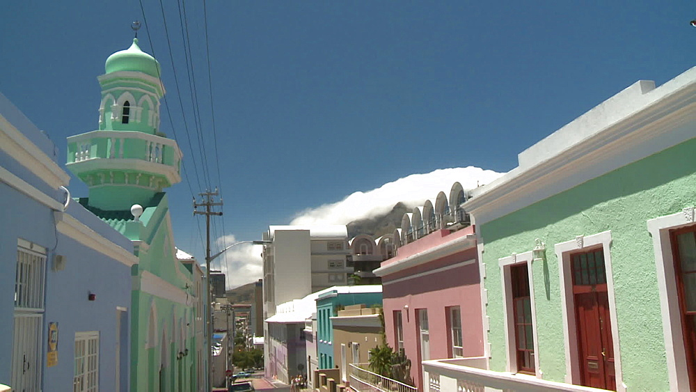 A row of Colourful houses next to a Mosque in a suburb, clouds coming over Table Mountain in the background, Cape Town, South Africa - 1182-187