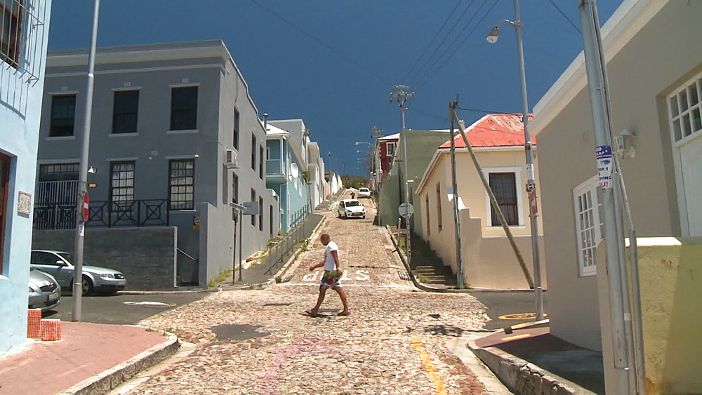 A quiet street in a suburb, a man walks across the street and a car comes down the street, Cape Town, South Africa - 1182-188