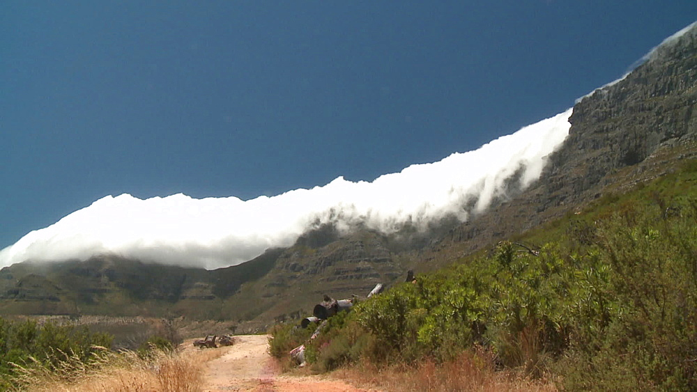 Clouds coming over Table Mountain 'Tablecloth' with a dirt road in the foreground, Cape Town, South Africa - 1182-189