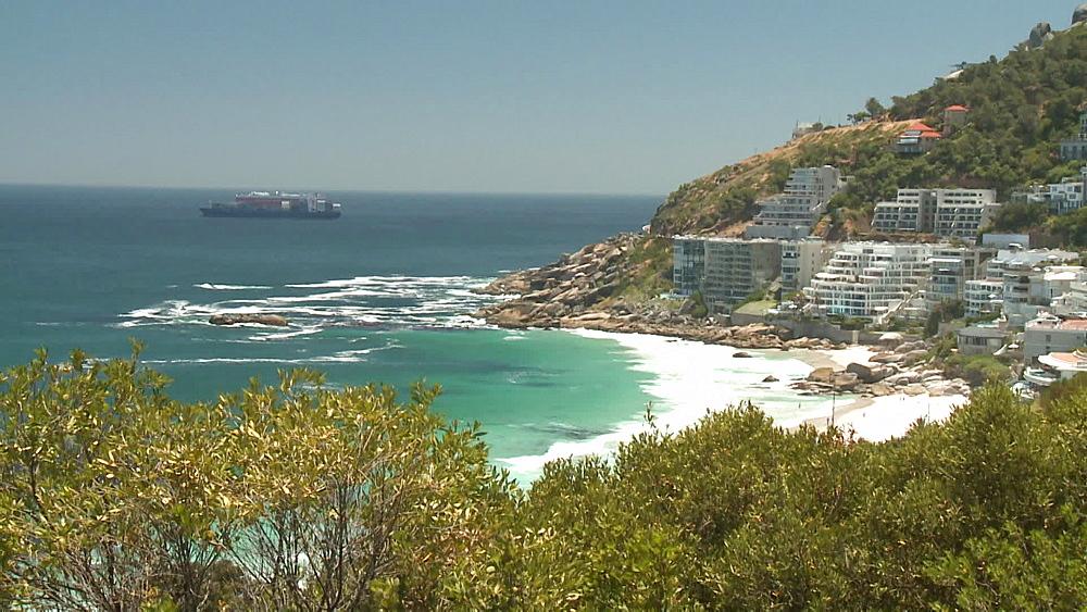 A cargo ship, container ship on the Atlantic Ocean, leaving Cape Town, Clifton Beach and apartments, flats in Clifton Beach, Cape Town, South Africa - 1182-200