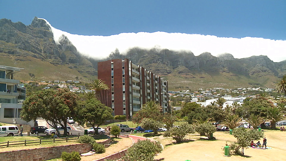 Table Mountain with clouds rolling over, apartment block, suburb in Clifton Beach, Camps Bay, Cape Town, South Africa - 1182-203