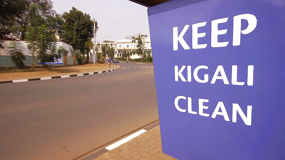 'Keep Kigali Clean' sign with cars, motorbikes, motorcycles driving past on a road in Kigali, Rwanda