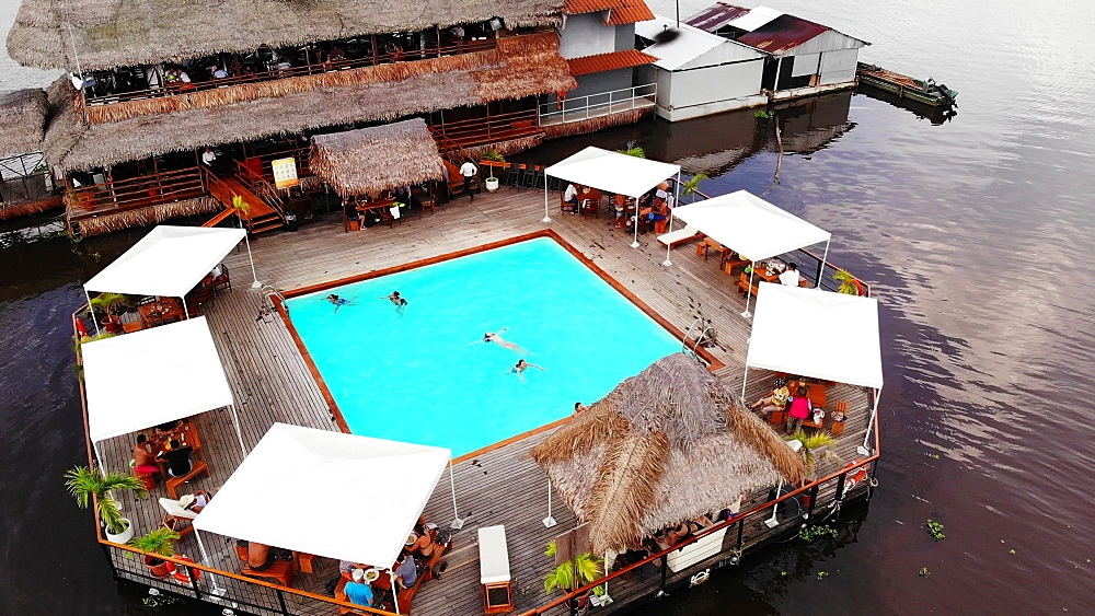 Aerial drone shot of Al Frio y Al Fuego floating restaurant in the Amazon River, Iquitos, Amazon, Peru, South America