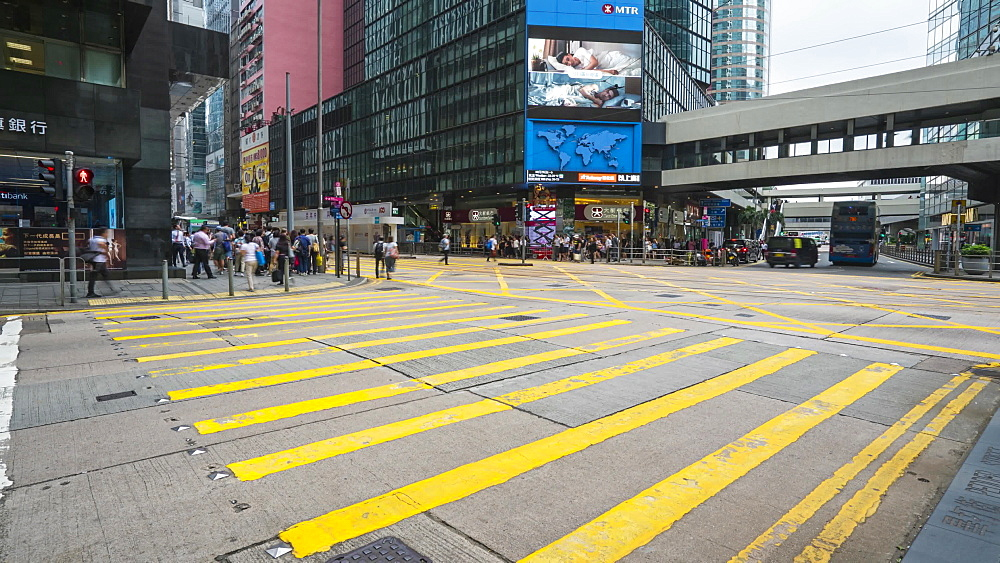 People crossing busy junction in Central, Hong Kong's financial district, time lapse, Hong Kong, China, Asia