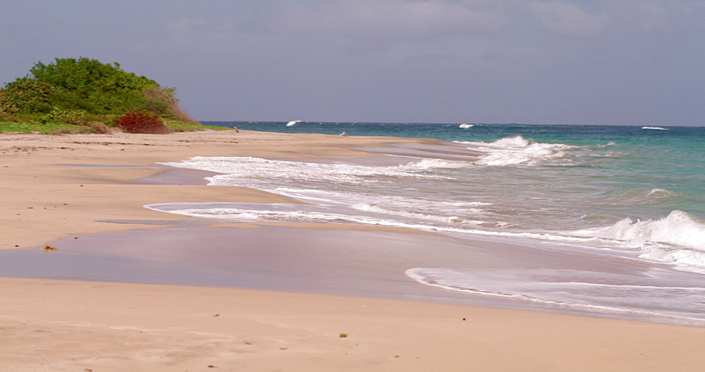 Waves lapping the shore onto Levera Beach, Grenada, Caribbean, West Indies.