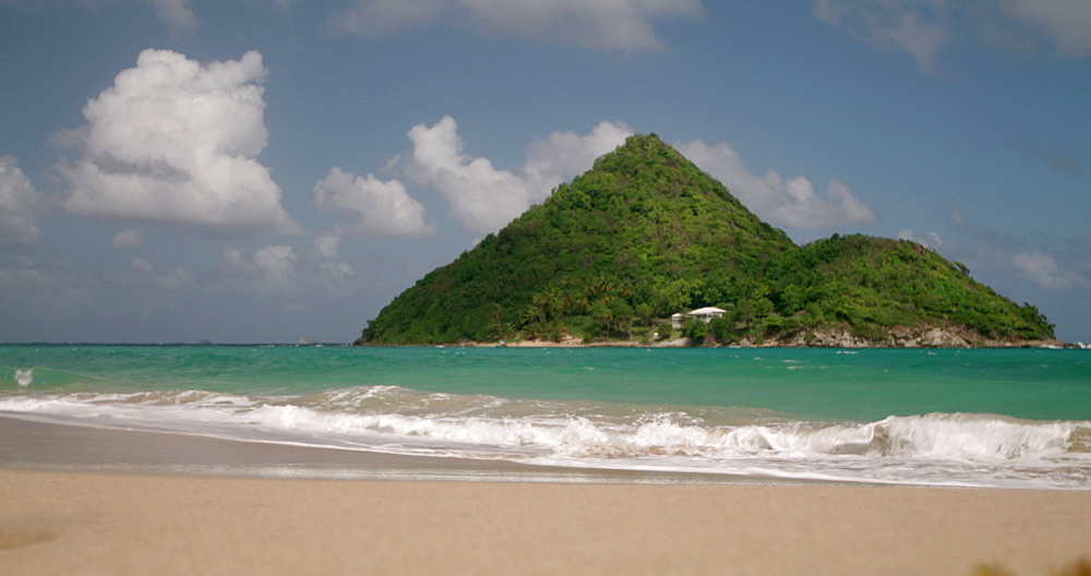 Waves lapping the shore and Sugar Loaf Island, Levera Beach, Grenada, Caribbean, West Indies.