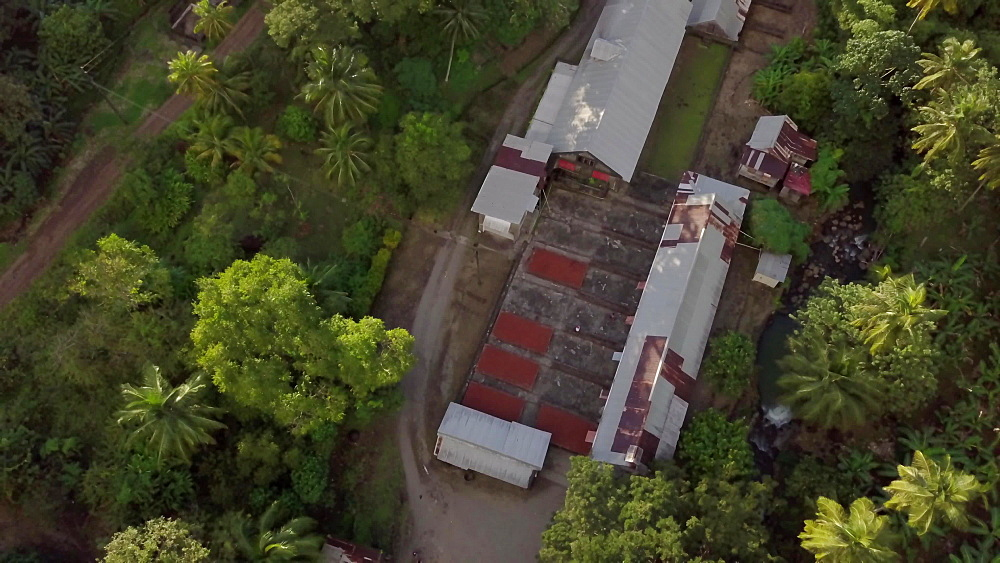 Drone aerial view of Dougaldston Estate of workers pushing the drying racks in, Gouyave, Grenada, West Indies, Caribbean, Central America - 1239-231