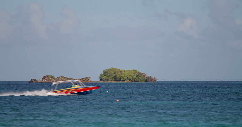 Speed boats going past a small island (islet) in the Caribbean Sea, viewed from Hillsborough Beach, Carriacou, Grenada, West Indies, Caribbean, Central America