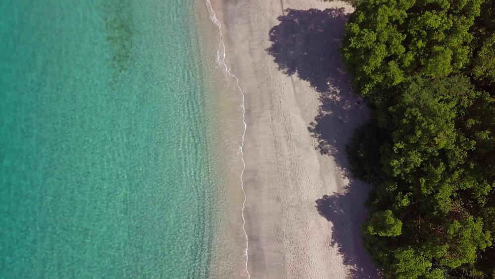 Drone shot along Caribbean Sea and Anse le Roche Beach, Carriacou, Grenada, Caribbean.