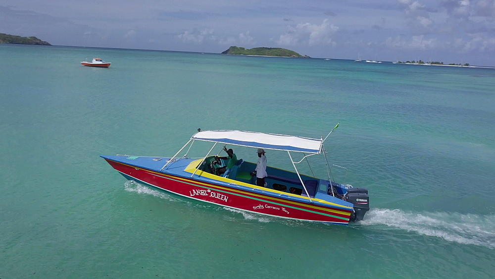 Occupants of a tour boat waving to drone, Paradise beach, carriacou, Grenada, Caribbean