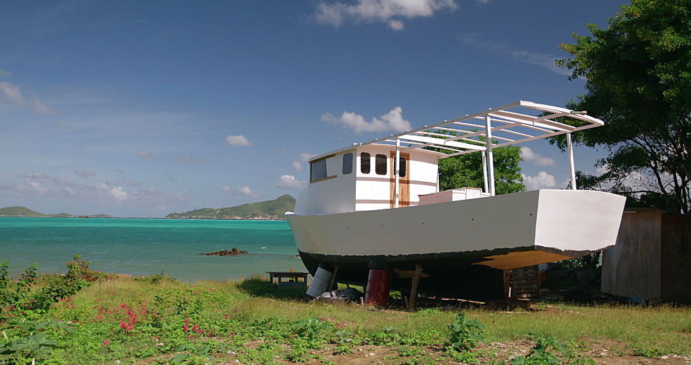 Traditional sloop boat being constructed with island views, Windward, Carriacou, Grenada, Caribbean.