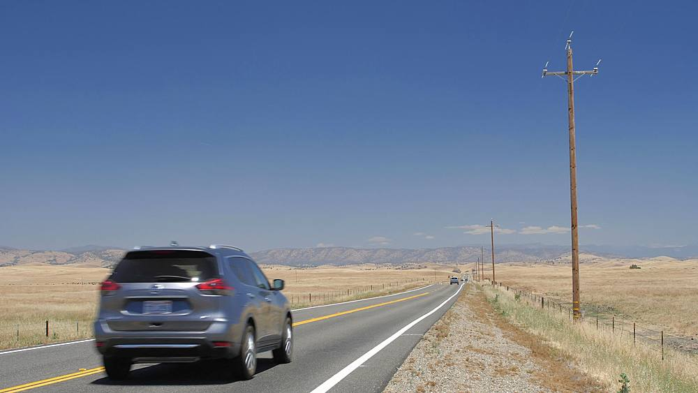 Cars on highway with electricity poles on the side, California, USA, North America