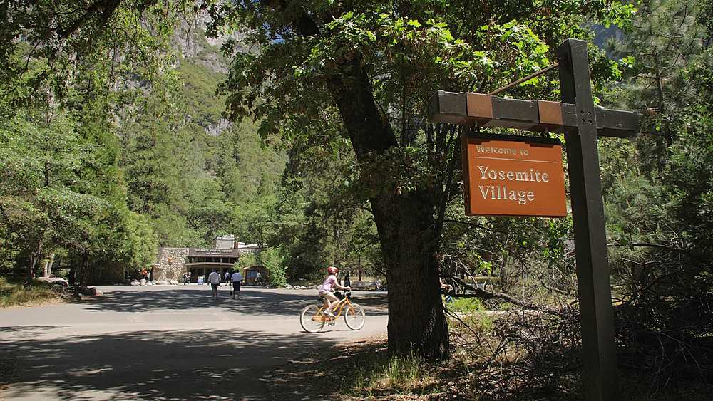 View of Yosemite Village sign, visitors and Visitors Centre, Yosemite Village, Yosemite National Park, UNESCO World Heritage Site, California, USA, North America