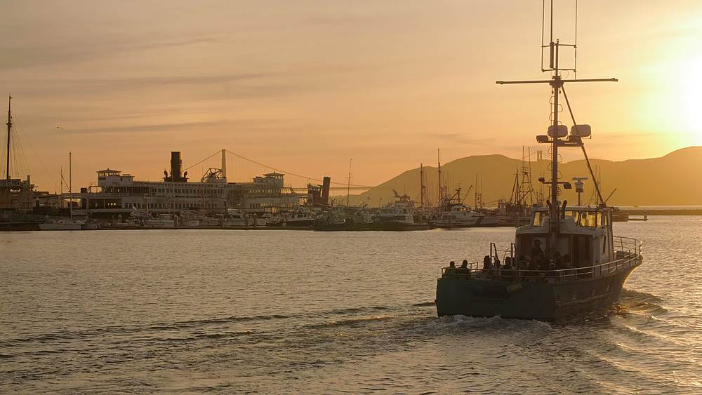 View of Fishing Boat leaving harbour from Fishermans Wharf at sunset, San Francisco, California, United States of America, North America
