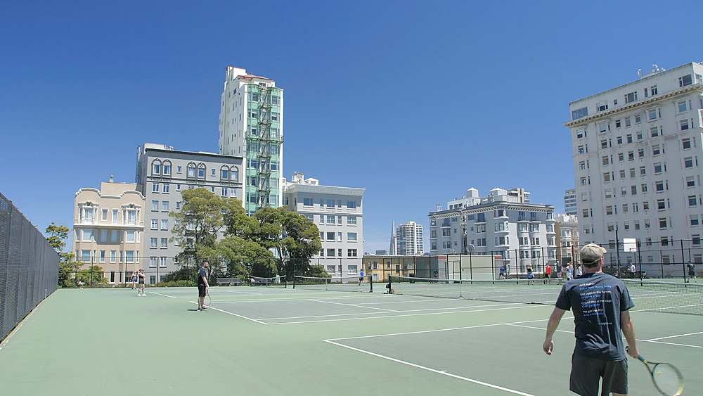 People playing Tennis in court with Transamerica Pyramid in the background, San Francisco, California, USA, North America