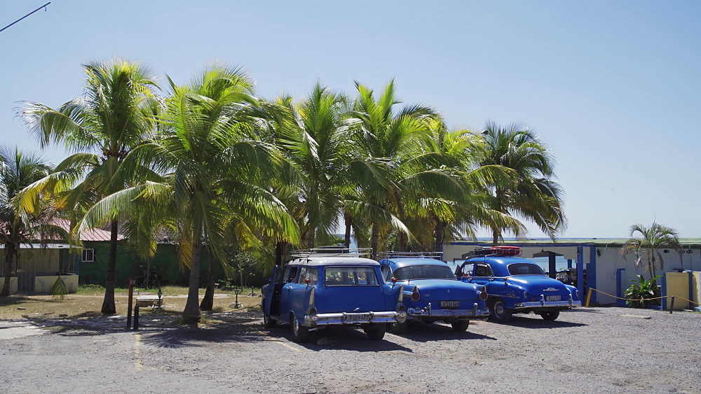 Old American and Russian vintage cars parked near beach in Cienfuegos, Cuba, West Indies, Caribbean, Central America